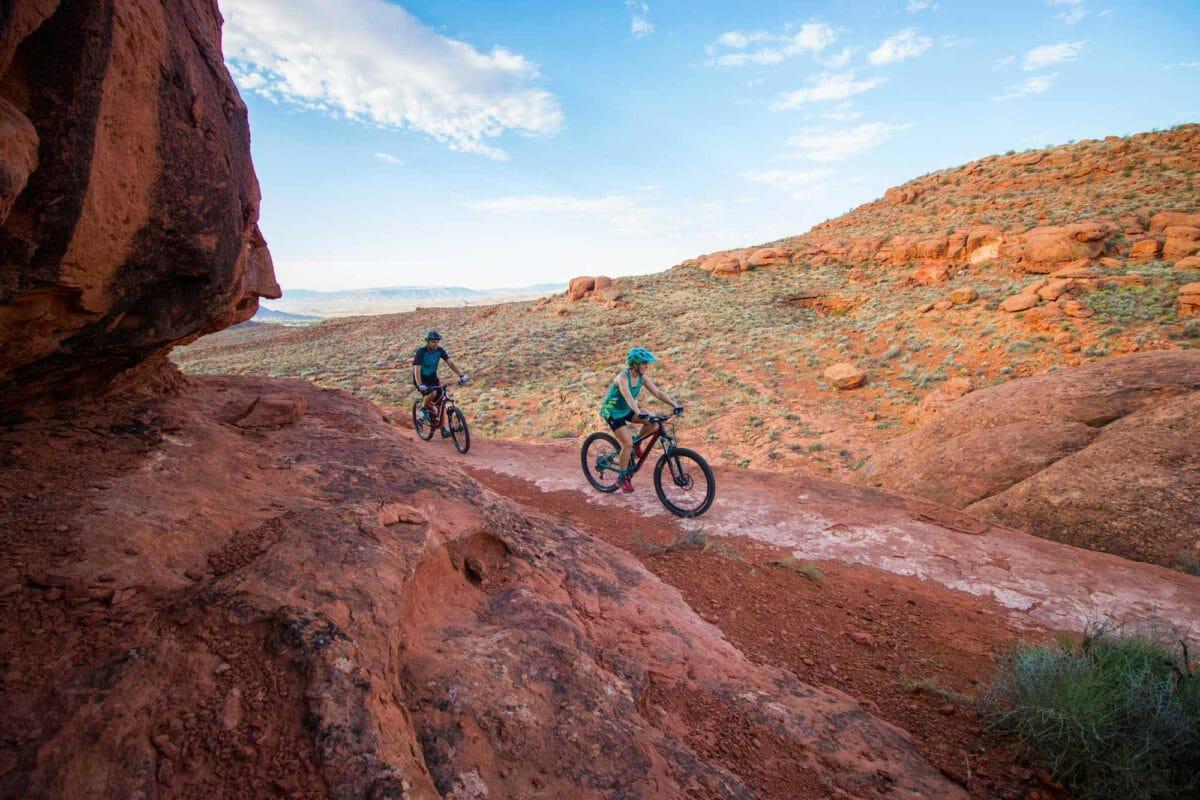 Mountain biking couple on desert trail.