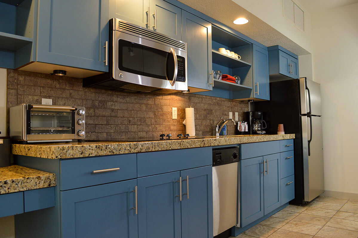 Kitchen in hotel suite with blue cabinets and granite counters and stainless steel appliances