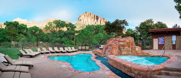 Outdoor pool and hot tub with faux rock waterfall and mountain views