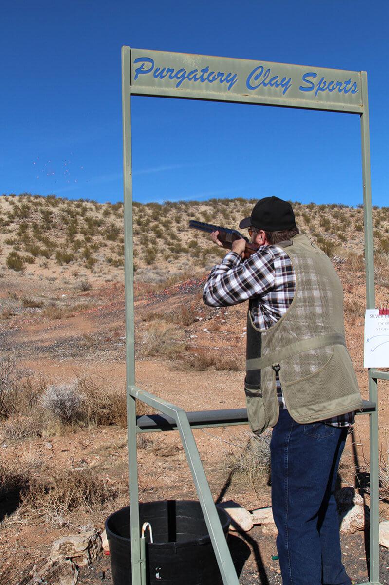 Man shooting shotgun from behind sign reading Purgatory Clay Sports