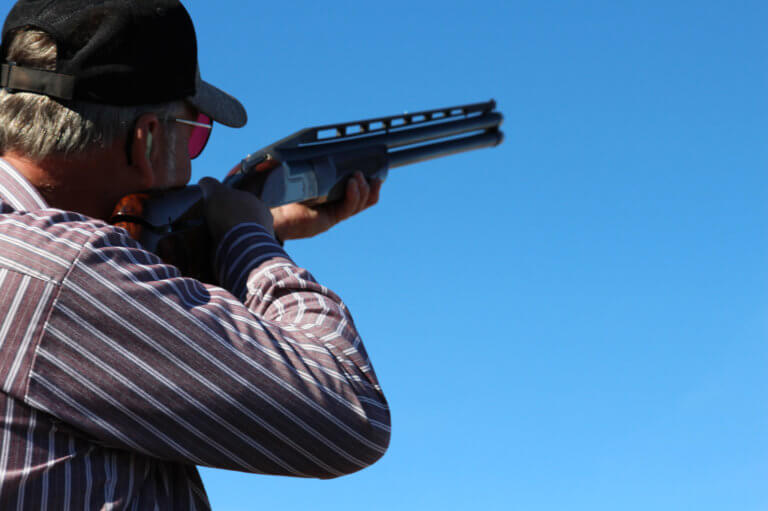 Man aiming shotgun into the sky