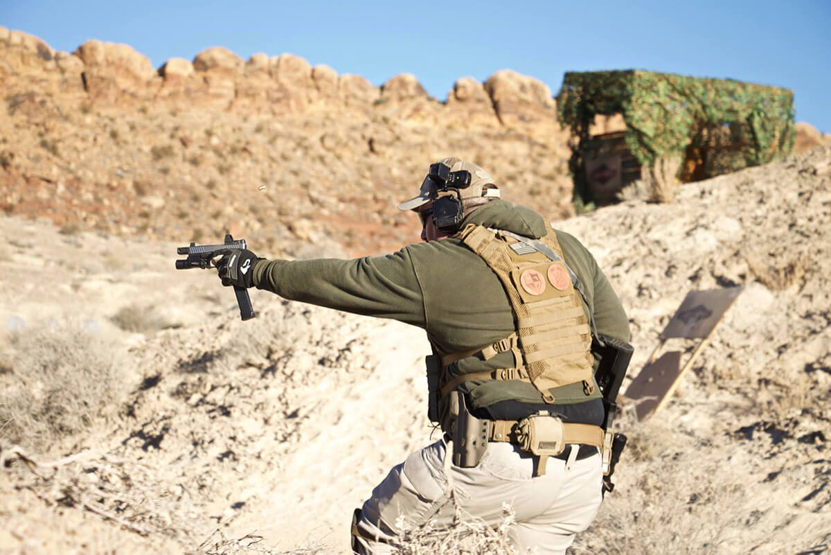 Man in tactical gear shooting a pistol