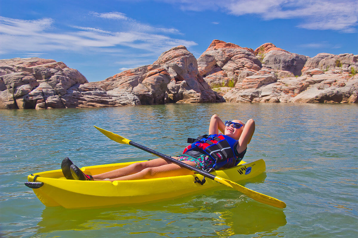 Young girl kayaking in desert lake