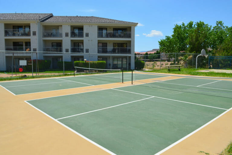Tennis court with apartment complex behind