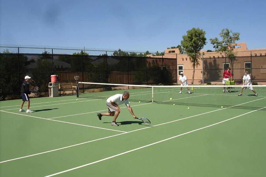 Tennis player reaching down for shot