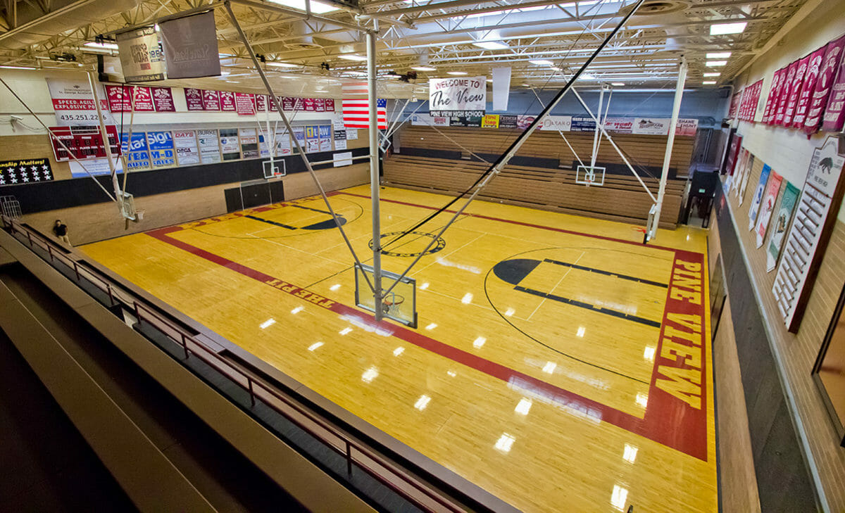 Wide view of indoor basketball court with polished wood floor