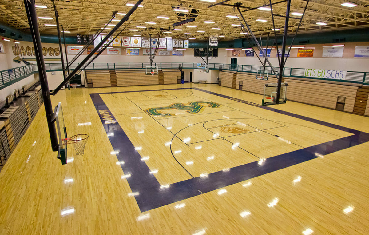 Wide-angle view of indoor basketball court with wood floor