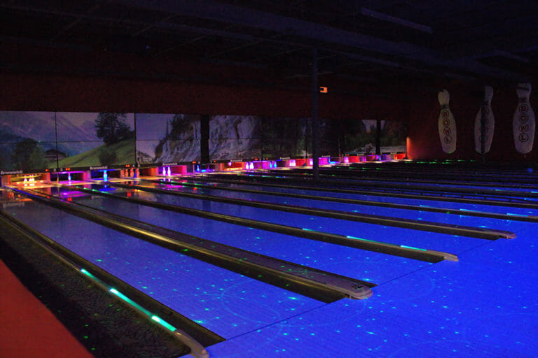 Glowing bowling lanes under black lights