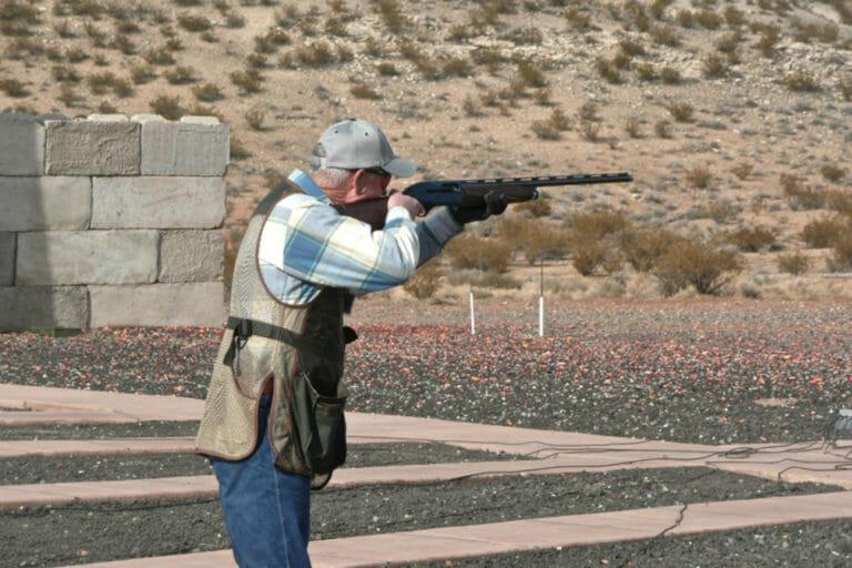 Mann, der Schrotflinte in der Wüste schießt