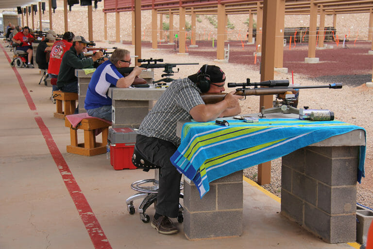 Wide view of seated men shooting rifles on range
