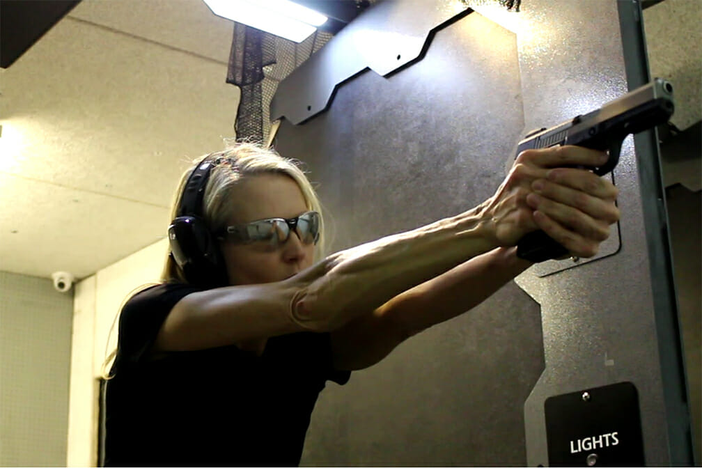 Woman shooting a pistol in indoor shooting range