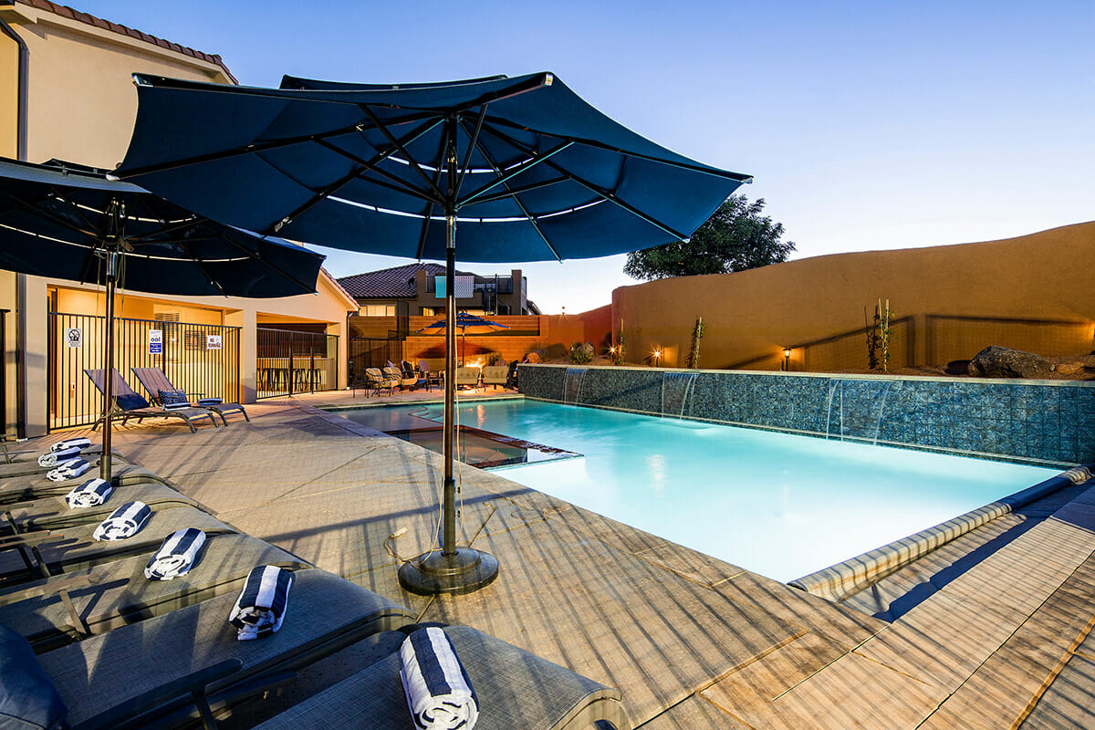 Outdoor pool with umbrella at dusk