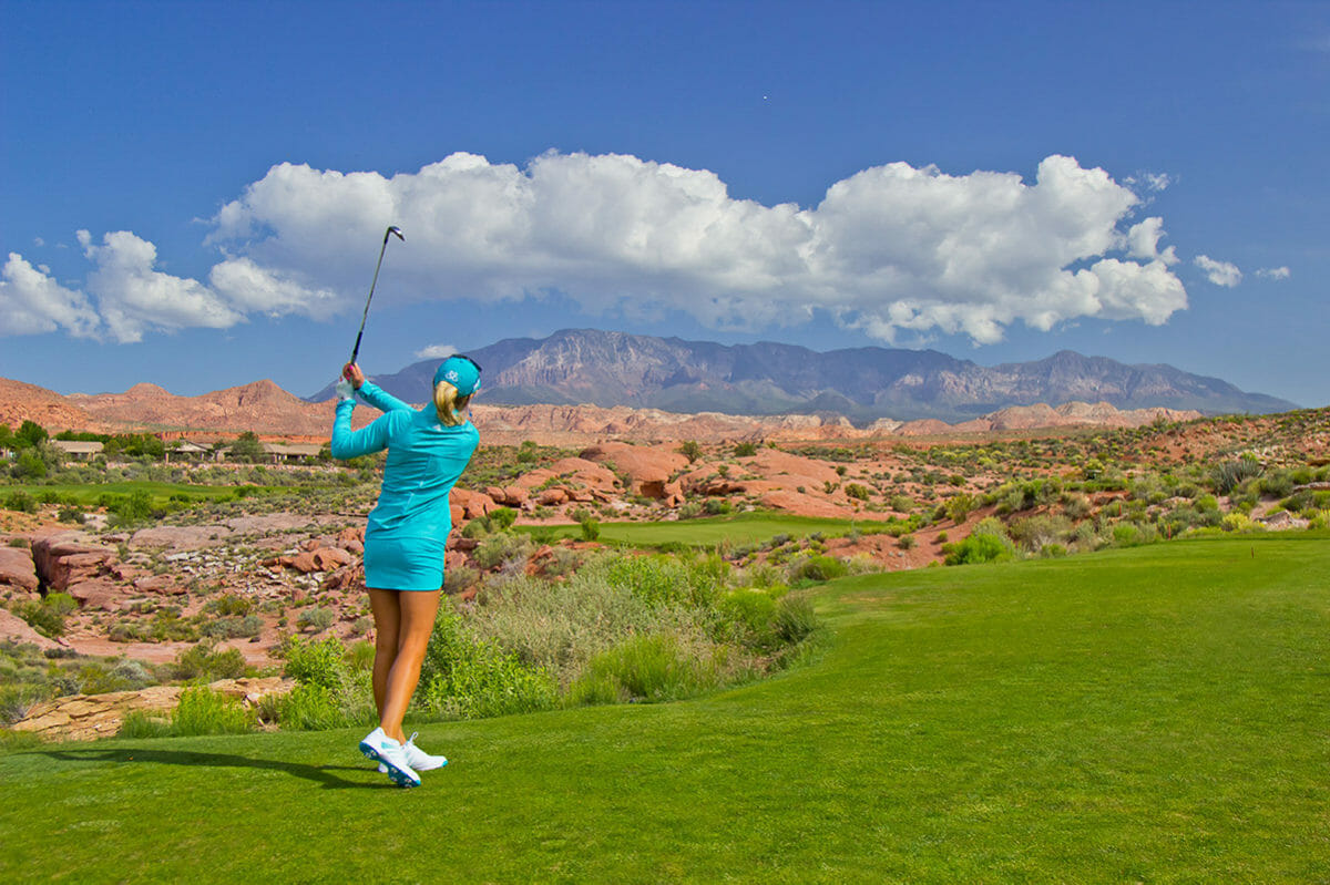 Female golfer midswing under blue sky with fluffy clouds.