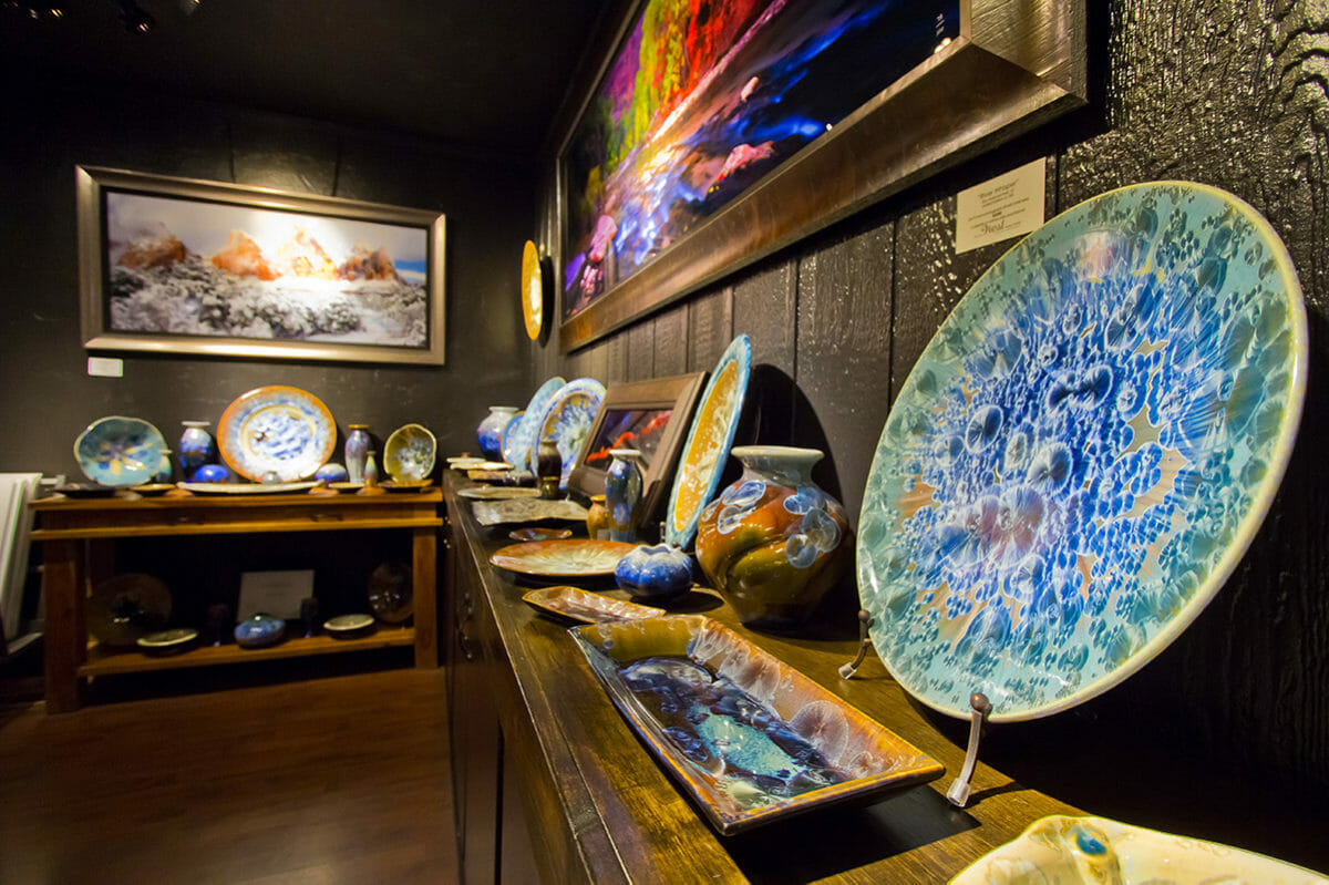 Close up view of pottery and paintings on display.
