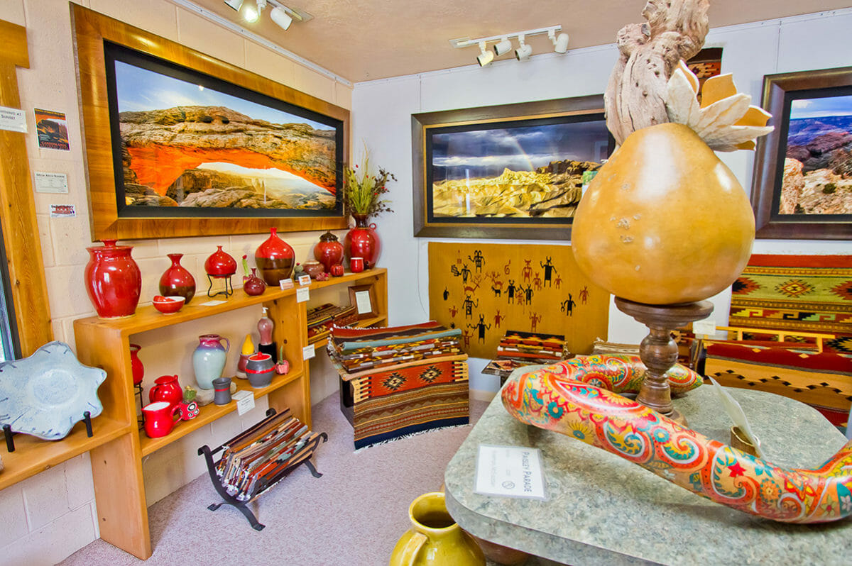Southwestern style paintings and pottery on display in art gallery.
