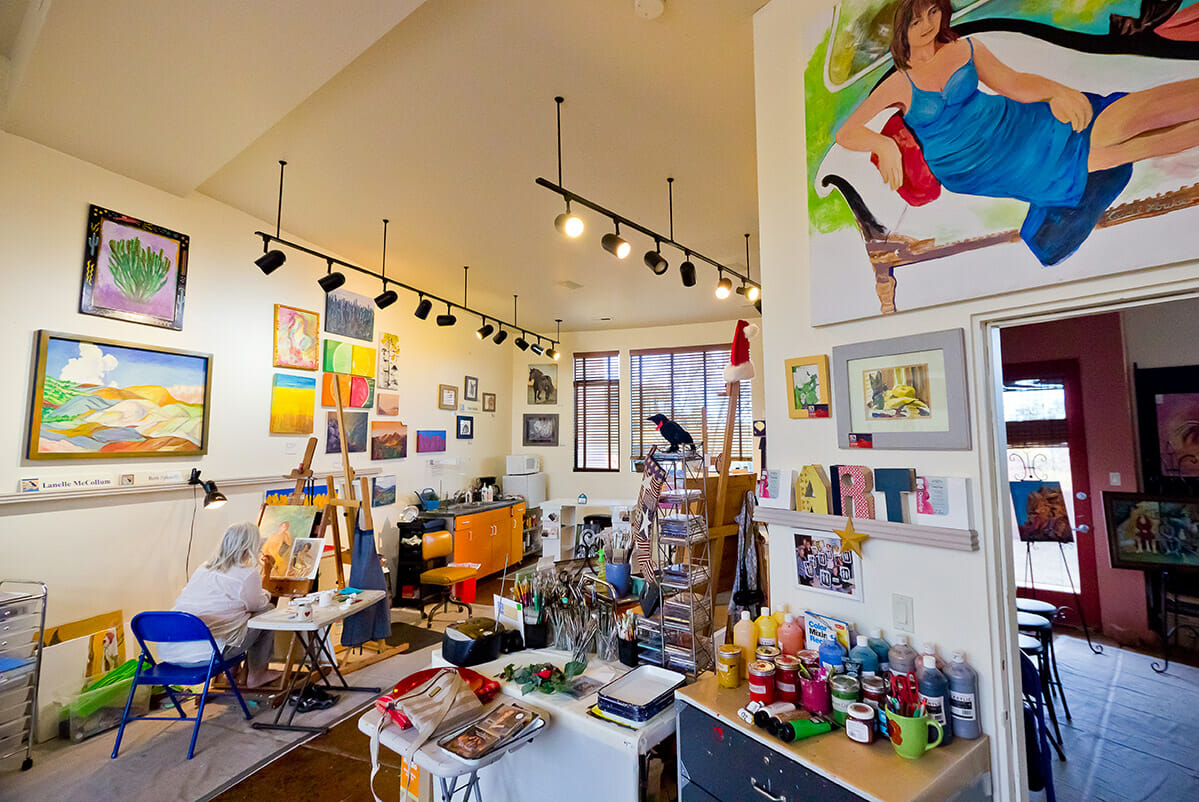 Künstlerin, die innerhalb der Galerie malt.