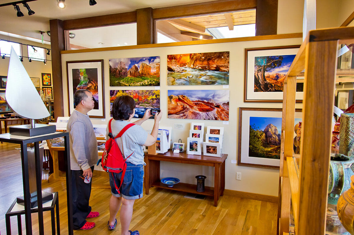 Couple admiring photographic prints on the wall of an art gallery.