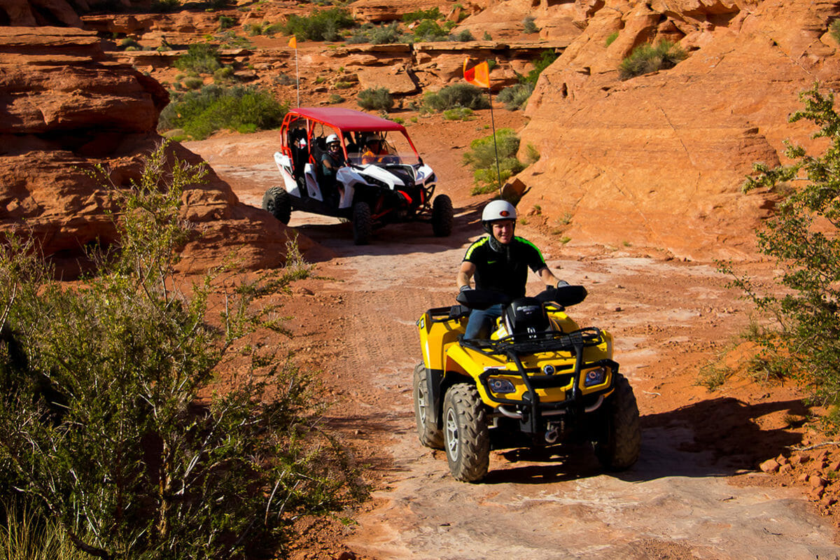 ATV leading UTV on tour through red rocks.
