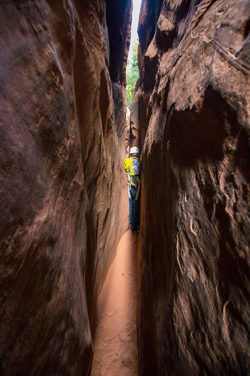 Man passing through tight slot canyon.