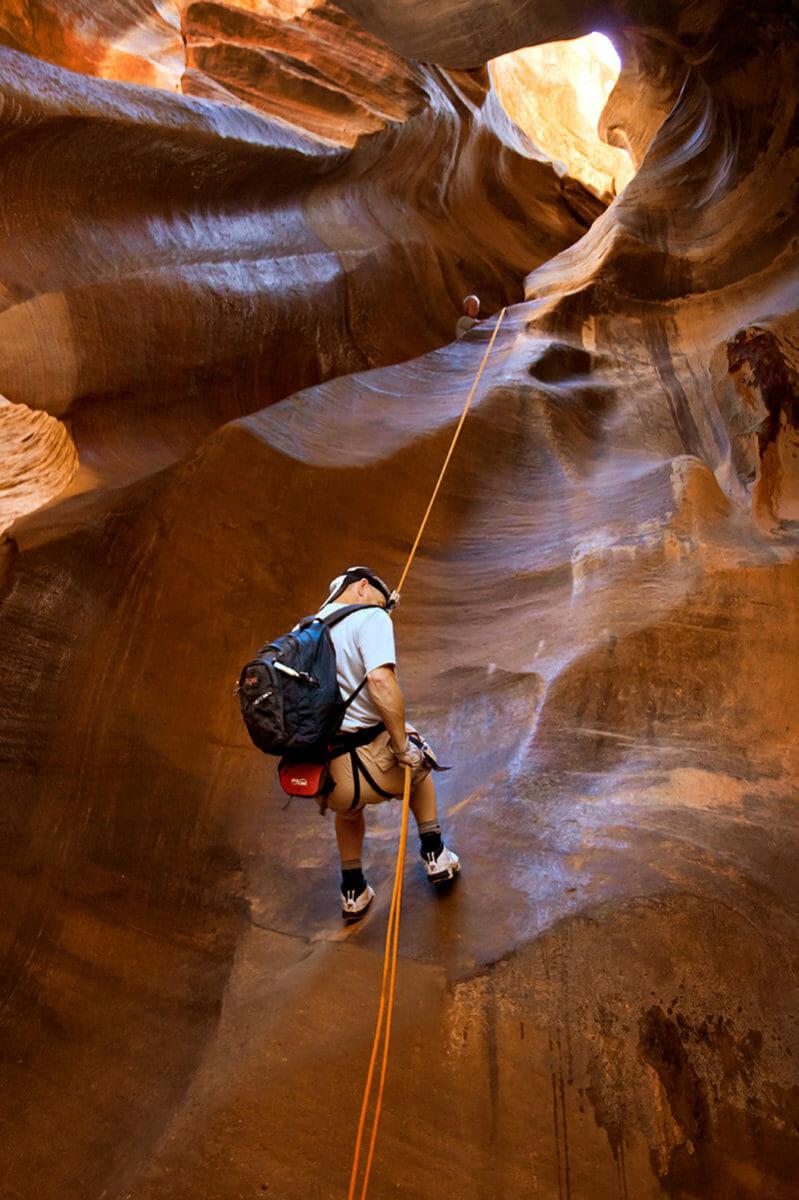 Man rappelling down slot canyon wall.
