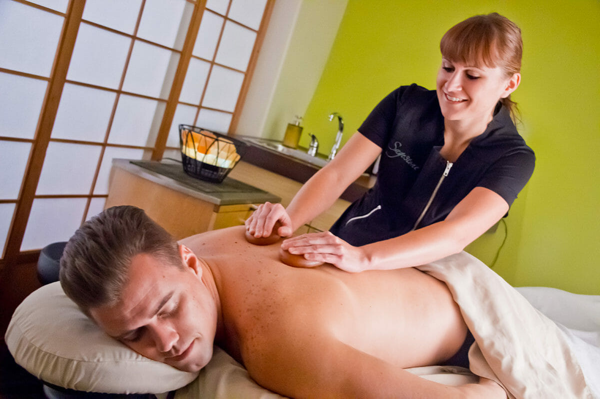 Man receiving a massage from smiling woman.