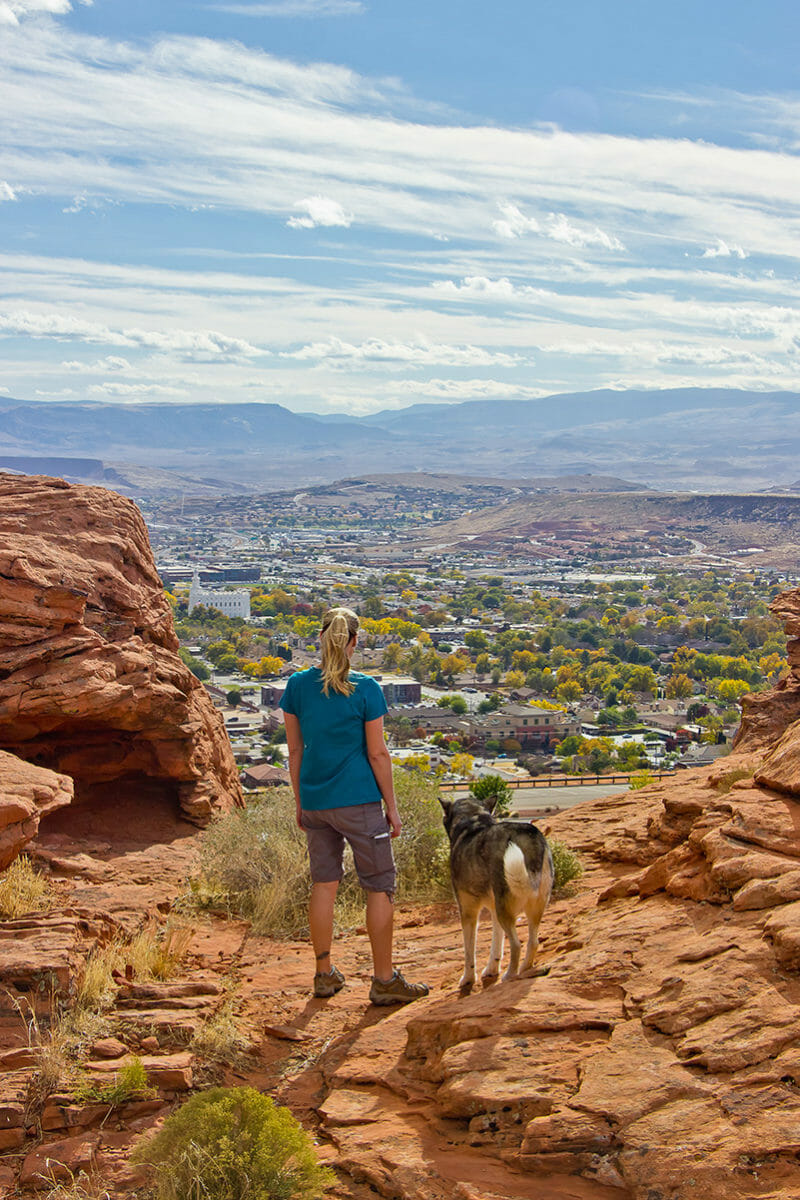 Woman hiking with dog overlooking the town below.