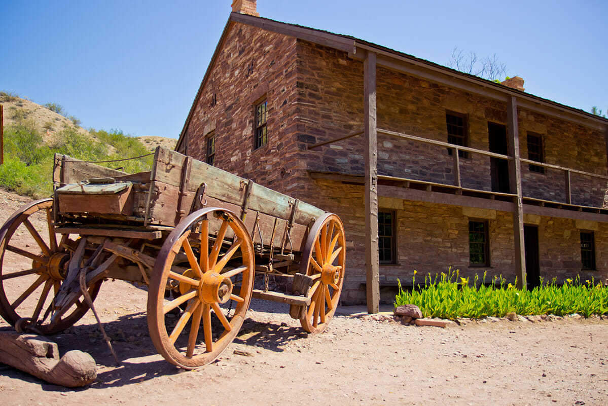 Old wooden wagon in front of brick building.