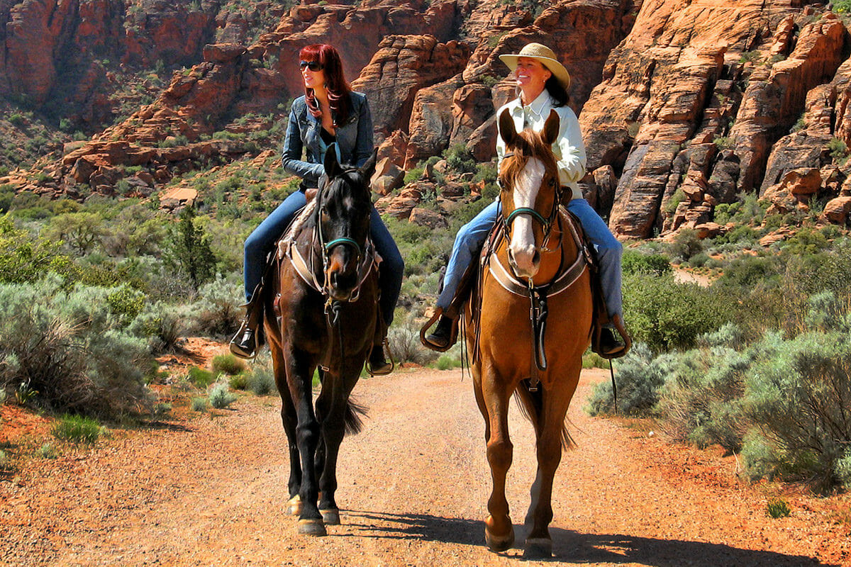 Two women riding horses through canyon.