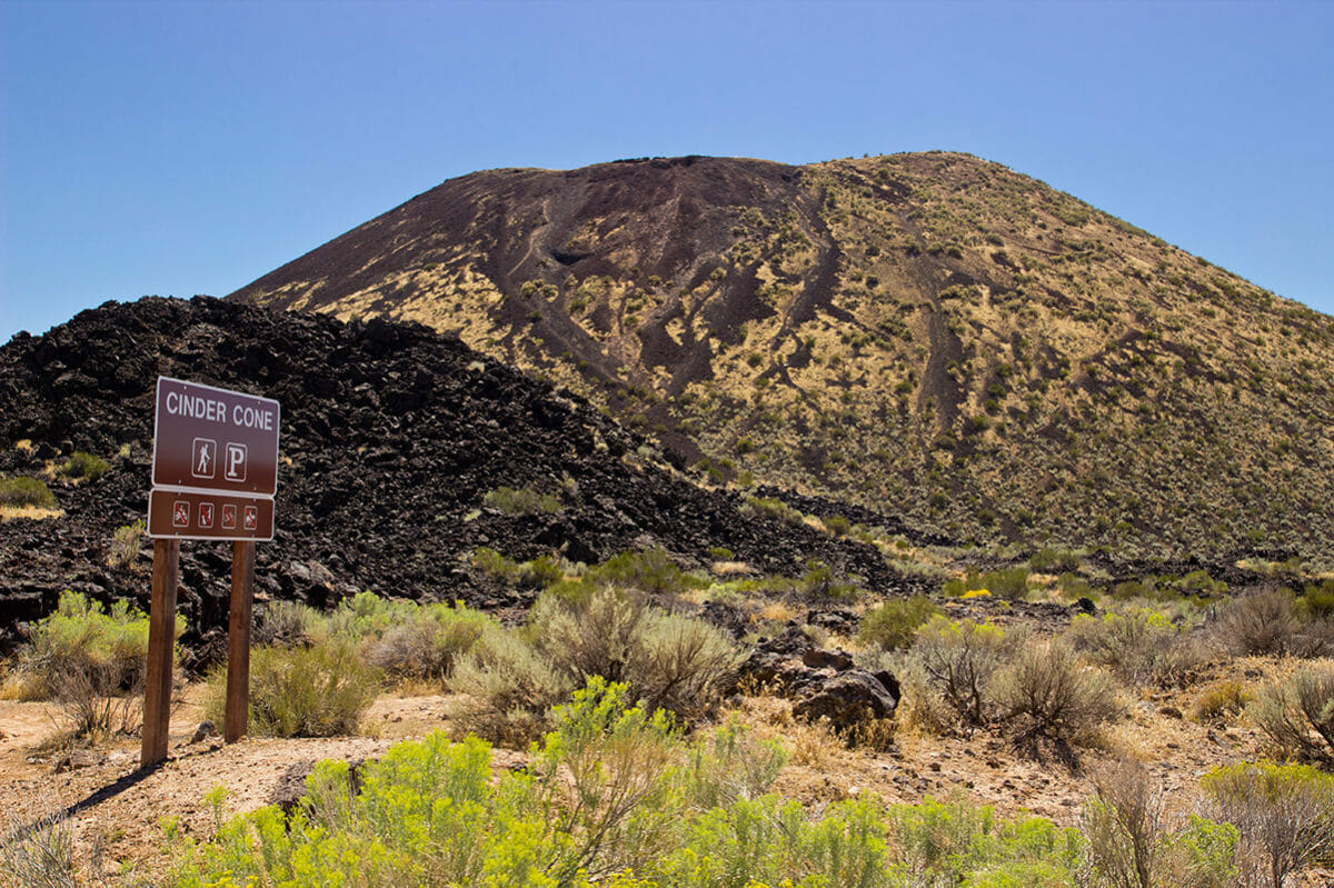 Volcanic cinder cone with trailhead sign.