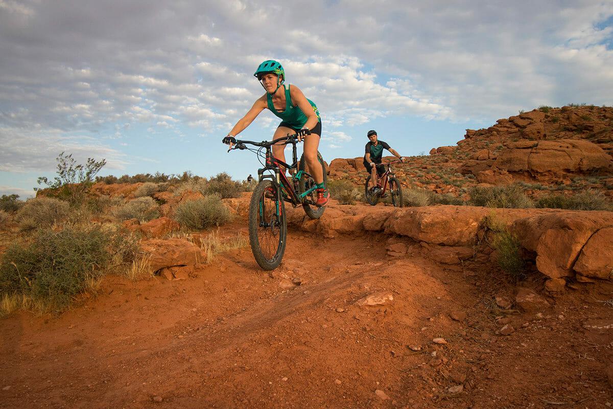 Couple mountain biking over rugged, red terrain.