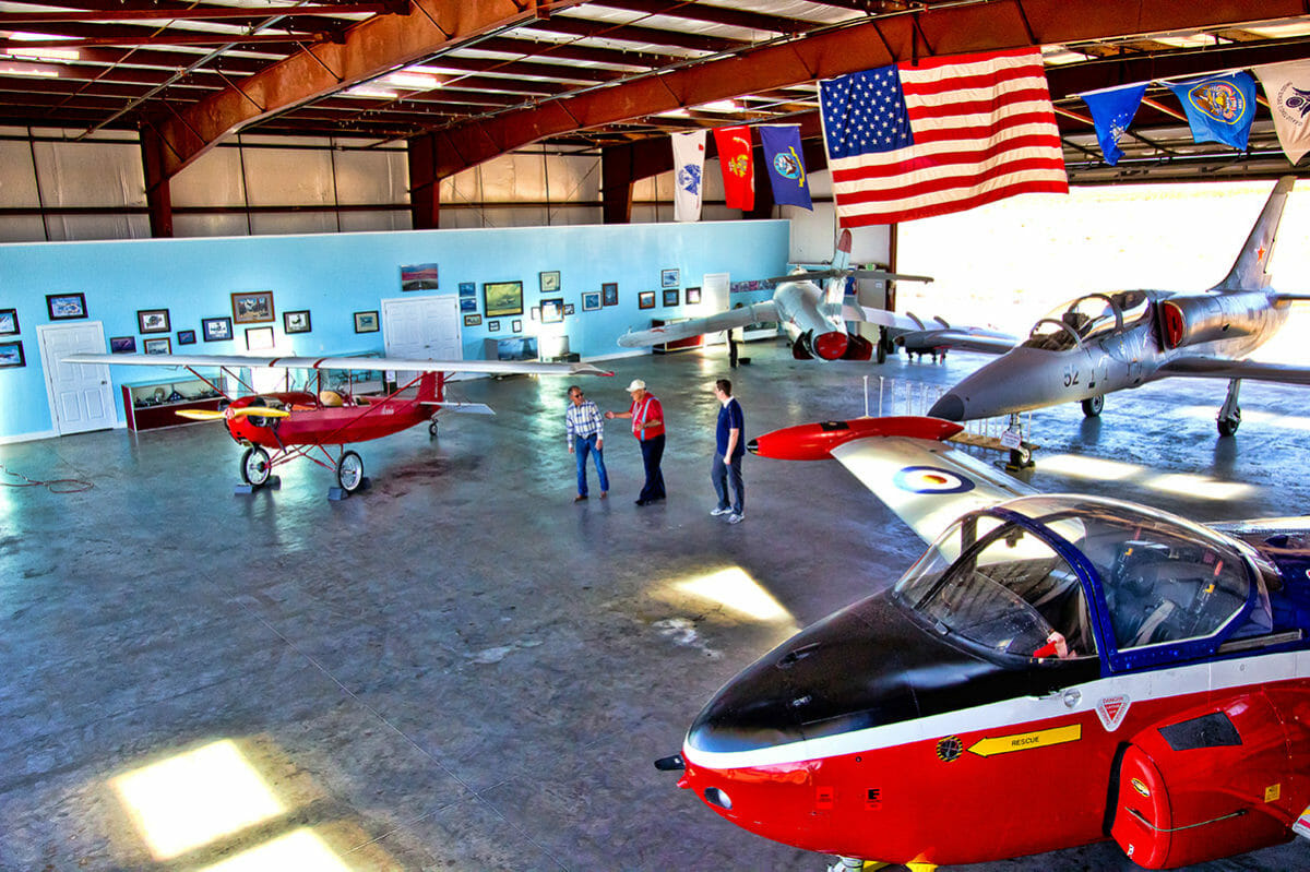 Docent speaking with two man in an airplane hanger filled with several classic aircraft.