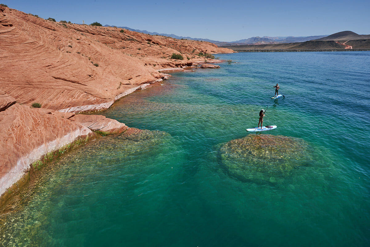 Couple on paddleboards on turquoise water with red rock formations in background.
