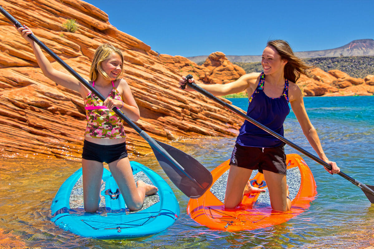 Young girls on paddelboards on turquoise water with red rock formations in background.