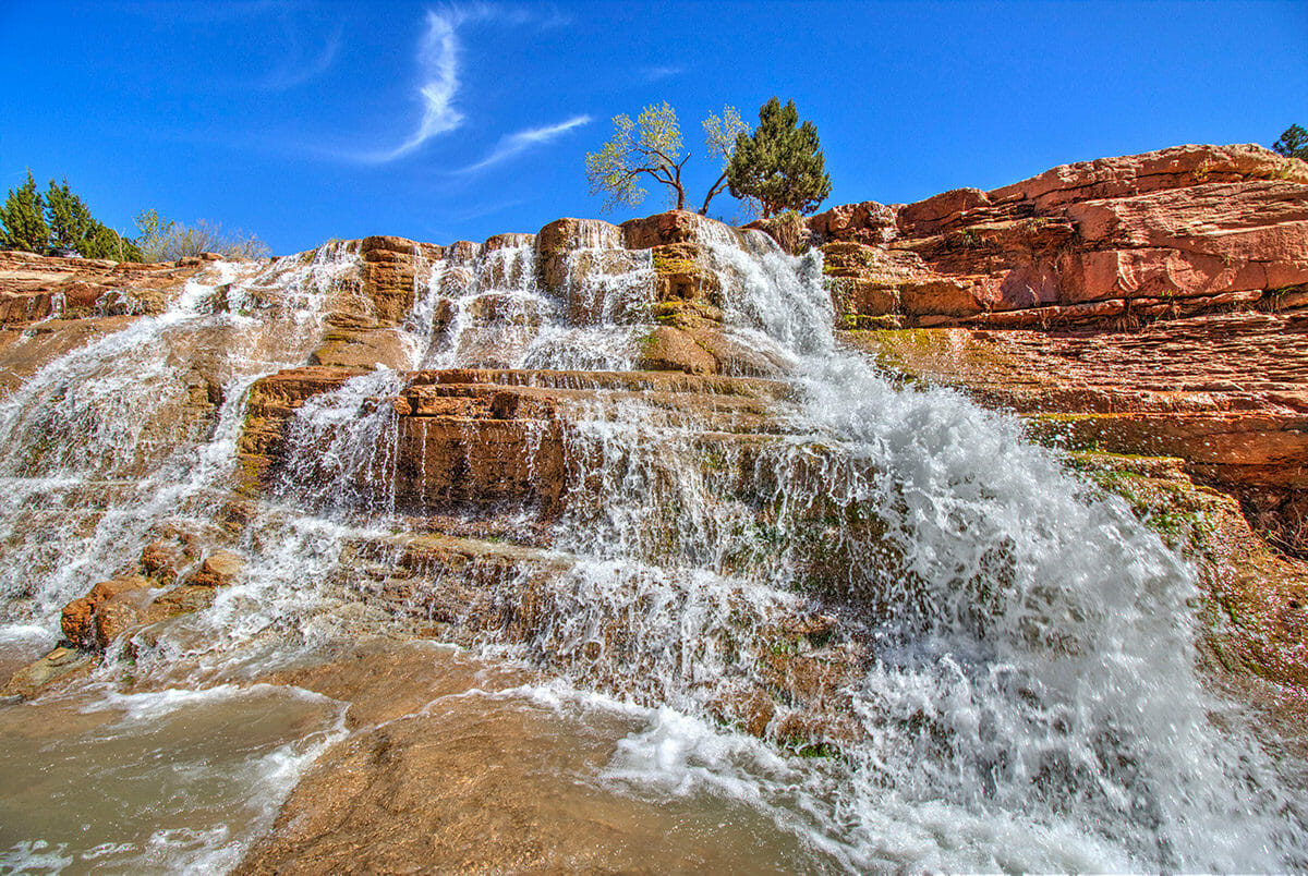 Waterfall pouring over red sandstone.