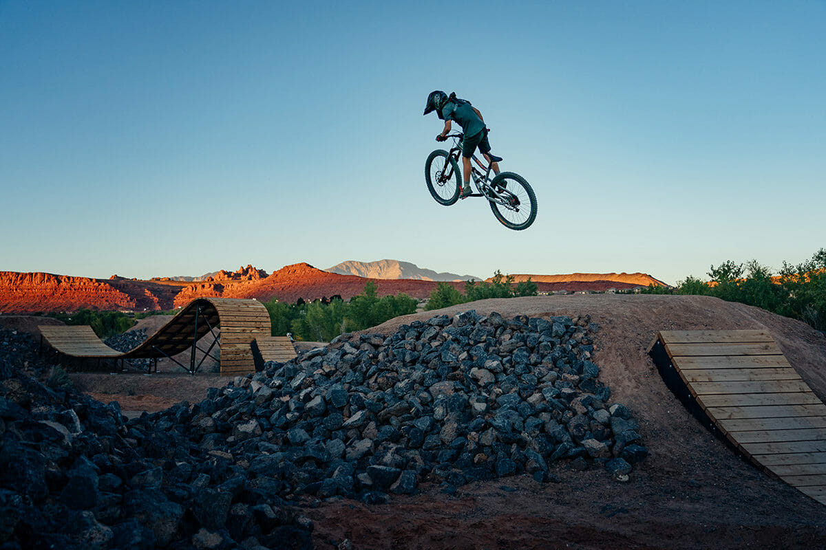 Mountainbiker flying off a wooden ramp.