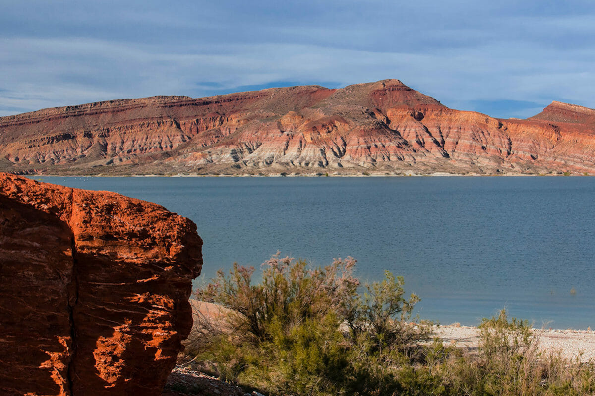 Scenic view with blue lake with red rock formation in foreground and background.