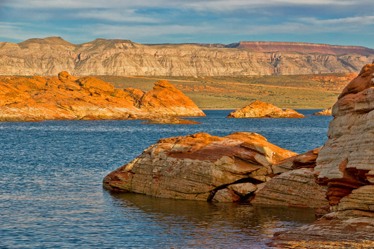 Blue waters with red rock formation interspersed throughout.