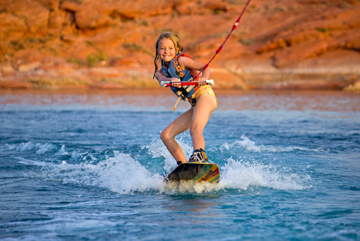 Smiling, young girl wakeboarding.