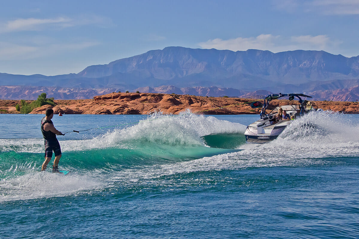 Man wakeboarding behind a boat on turquoise water.