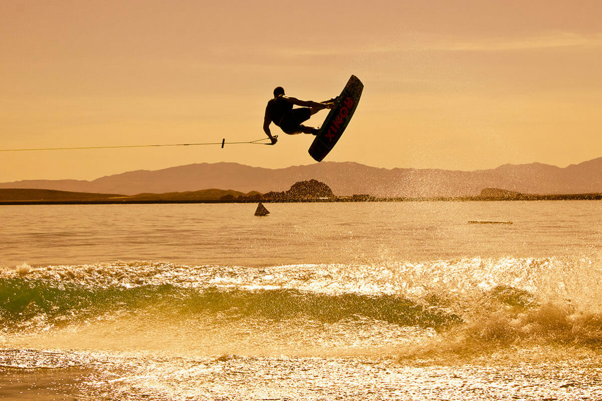 Silhouette of wakeboarding man flying through the air over the water at sunset.