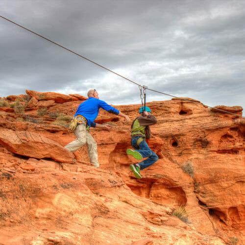 Mann, der Jungen von Klippe auf Zipline drückt.