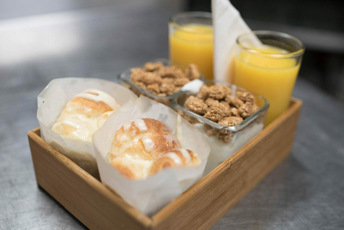 Breakfast tray with orange juice, yogurt parfait, and muffin