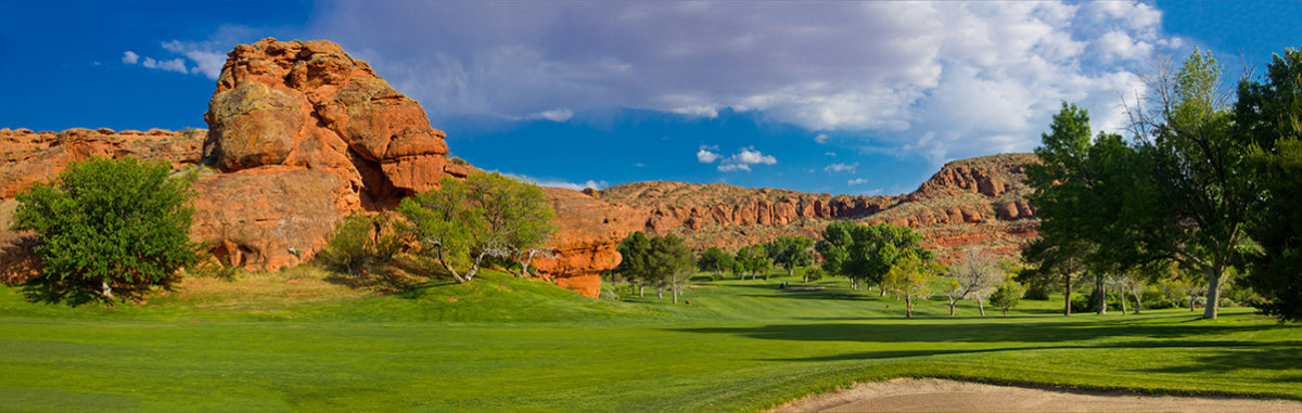 Panoramic view of desert golf course with red rocks