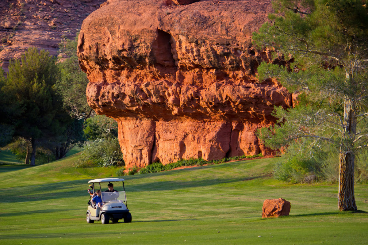 Father and son in golf cart on fairway in front large red rock formation.