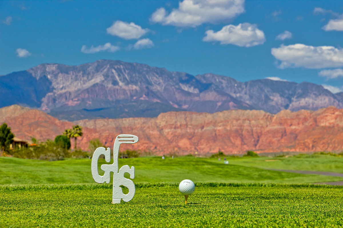 View of golf tee with large mountains in the background