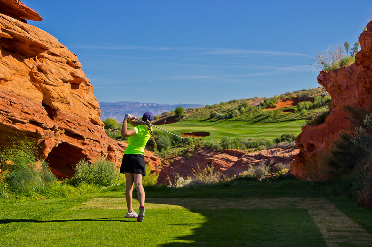 Woman golfing on desert course between red rocks