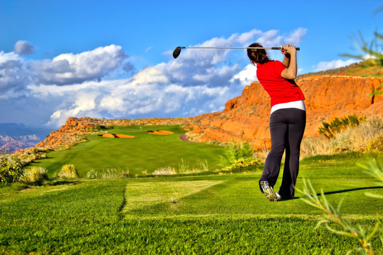 Woman golfing on desert course