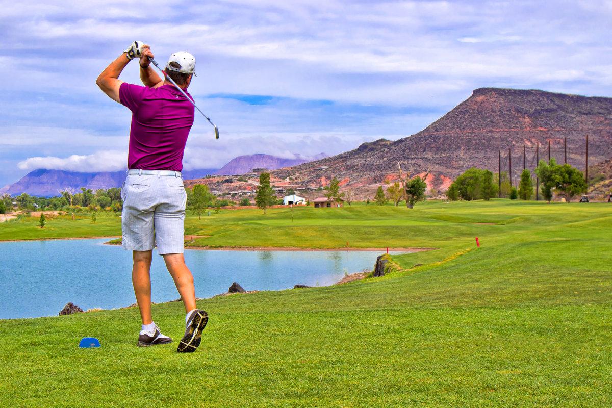 Männlicher Golfer im Mittelschwung vor kleinem Teich.