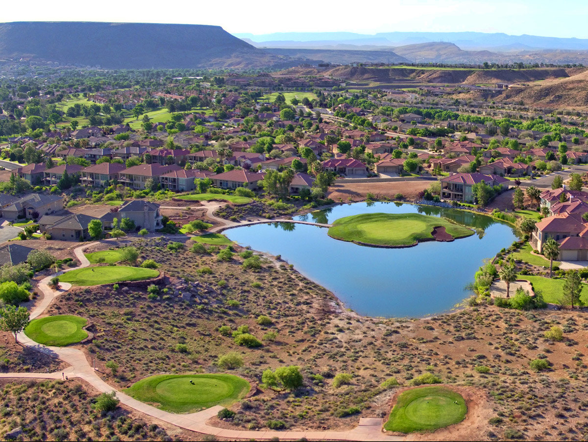 Aerial view of desert golf course with lava rocks and pond
