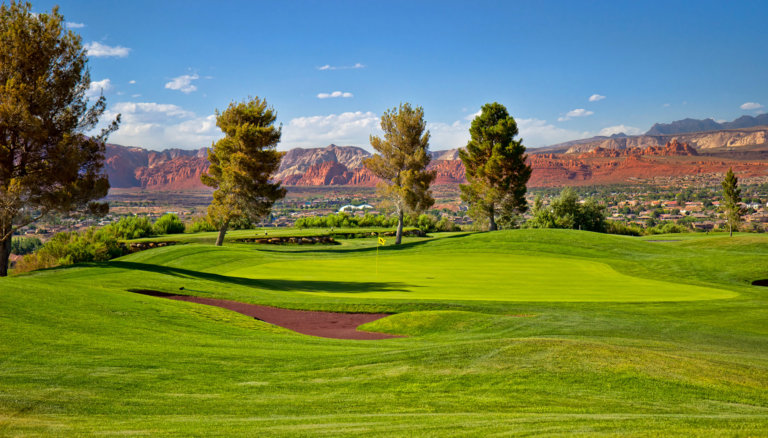 Green fairway with pine trees and red rock formation in background.